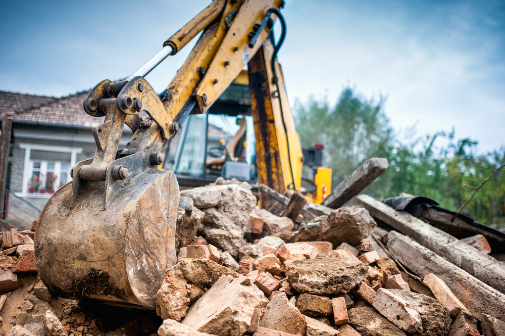A yellow excavator digs into a pile of bricks and other construction debris in front of a blue house.