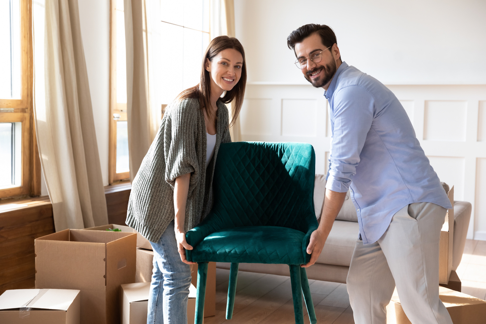 A male and female couple smile for the camera as they collectively move a green chair out of a room.