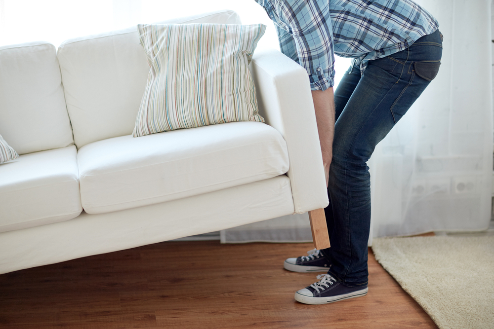 A man in a blue plaid flannel and jeans lifts one end of a white couch from the hardwood floor it rests on.